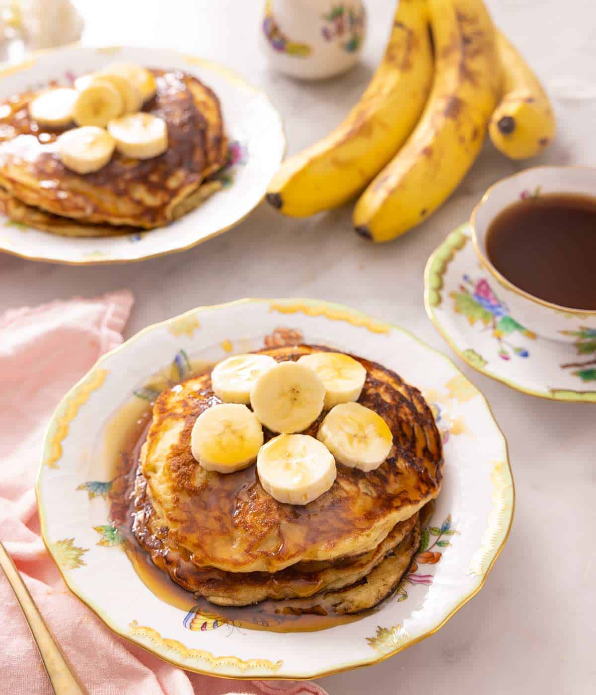 Banana pancakes on a plate topped with slices of banana