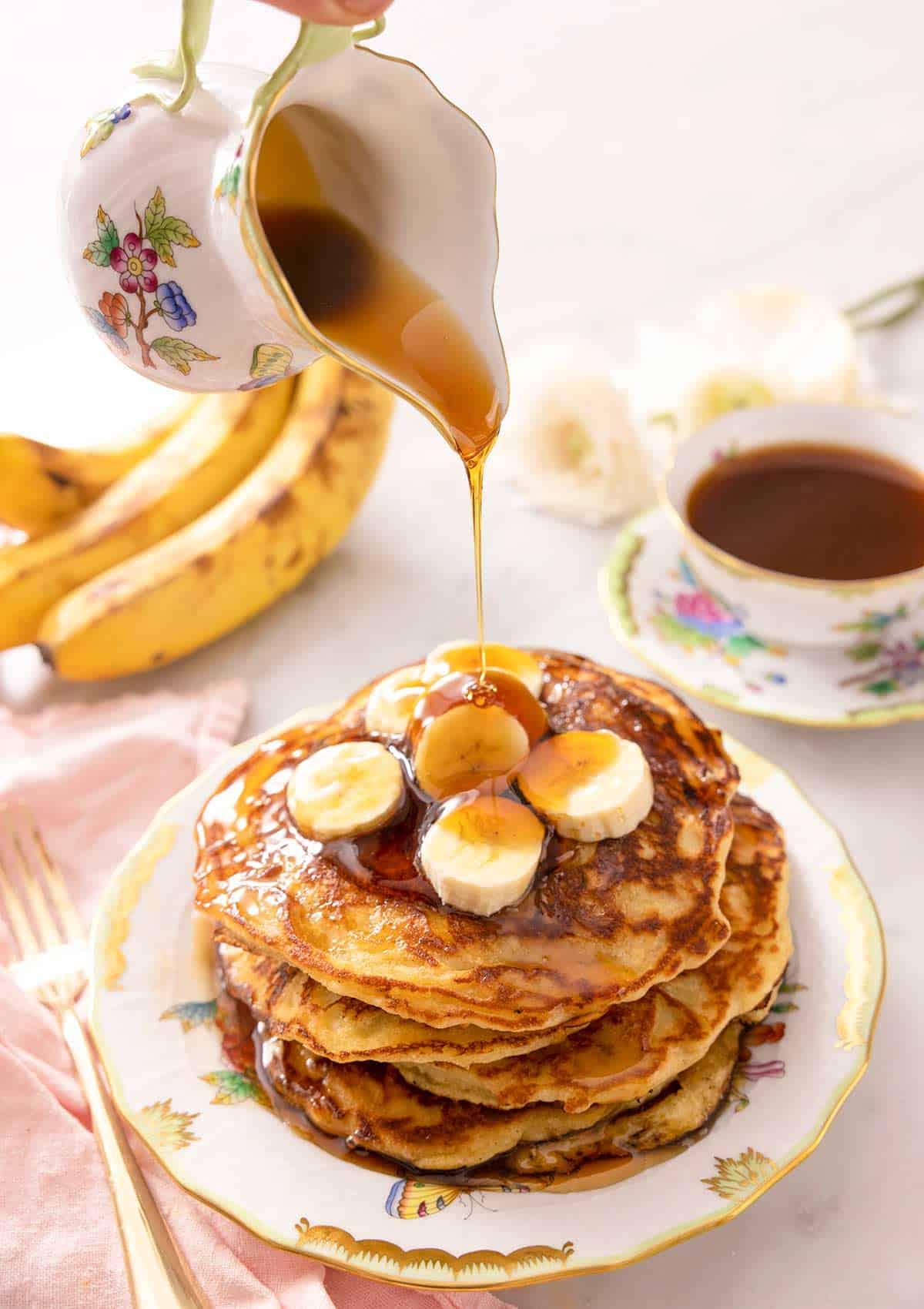 A jug powring syrup of banana pancakes