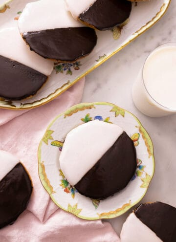 Overhead view of multiple black and white cookies with one in a plate beside a glass of milk.