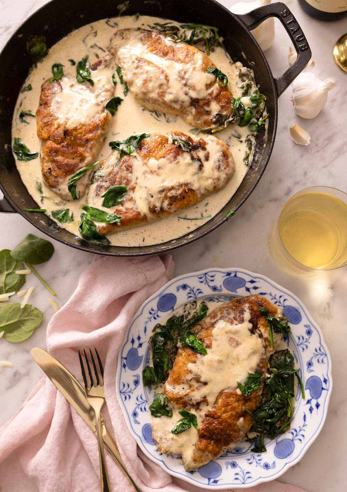 Overhead view of a braiser containing chicken florentine with a serving plated up beside it.