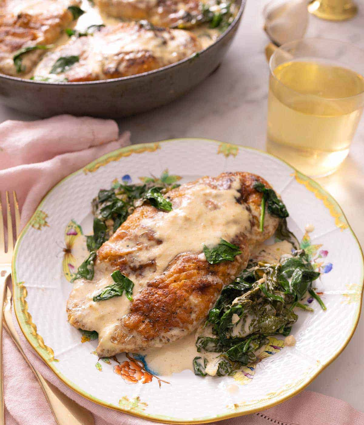 A plate of chicken florentine with the chicken breast coated in sauce and spinach.