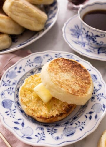 An English muffin cut in half and spread with butter on a plate