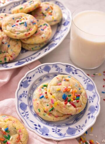 Funfetti cookies on a plate beside a glass of milk.