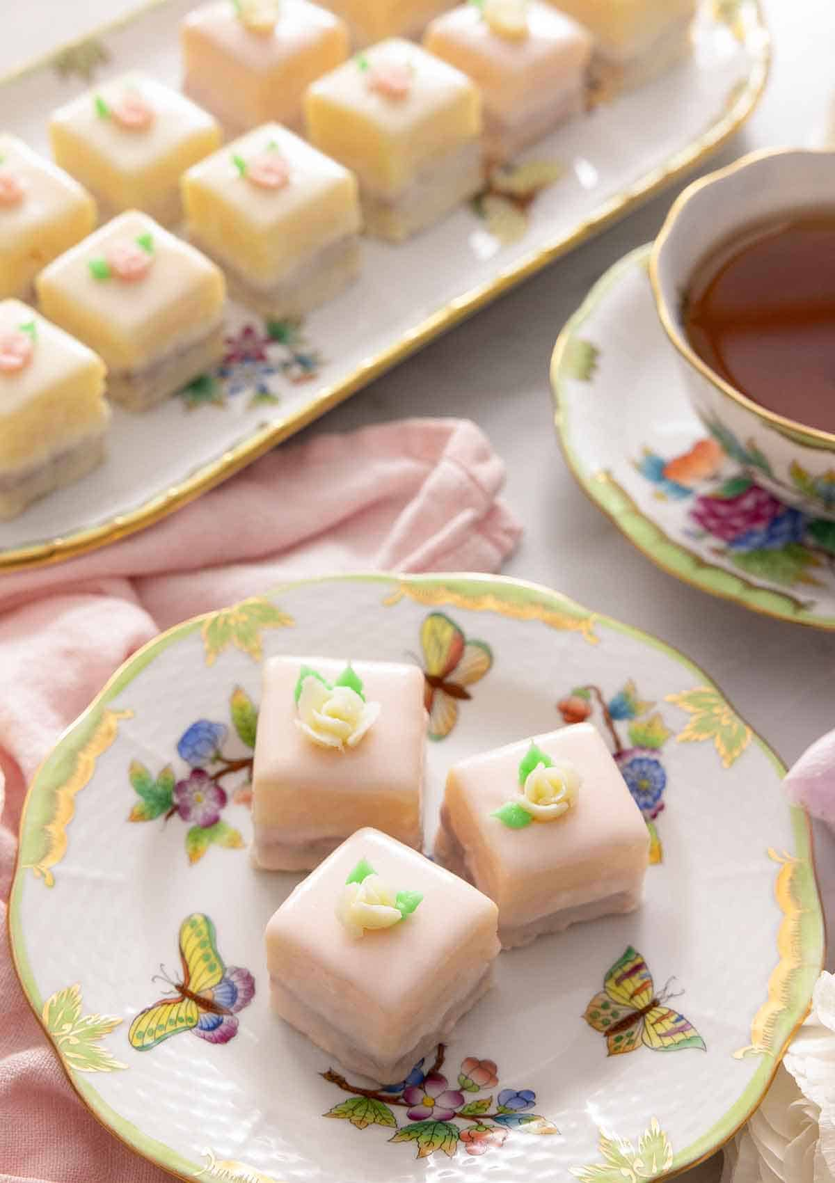 Overhead view of a serving platter of petit fours beside a plate with three.