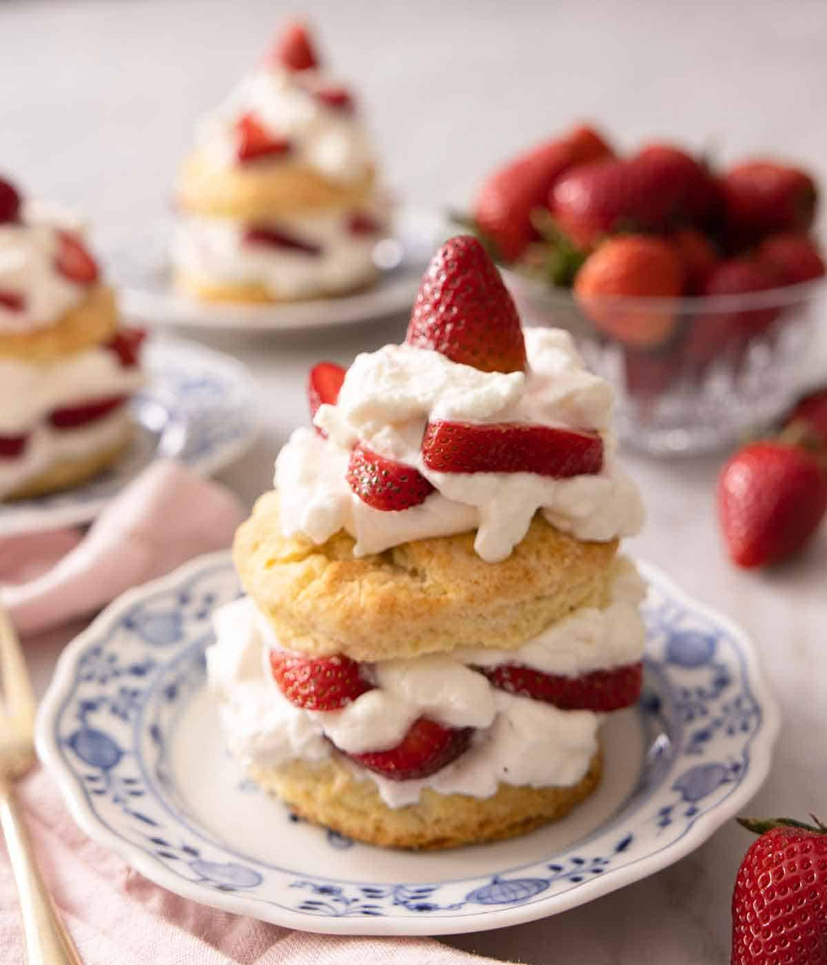 Three plates of strawberry shortcakes beside a bowl of strawberries with one plate in focus.