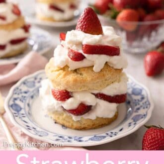 Pinterest graphic of a strawberry shortcake topped with whipped cream and strawberries on a blue and white plate.