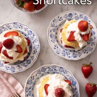 Pinterest graphic of an overhead view of three strawberry shortcakes by a bowl of strawberries. All cakes are topped with whipped cream and berries.