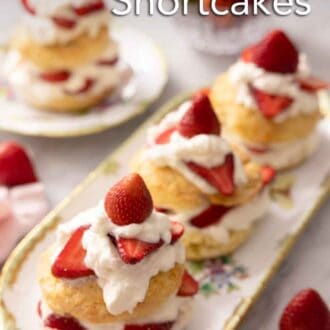 Pinterest graphic of a platter of three strawberry shortcakes topped with cream and sliced strawberries.