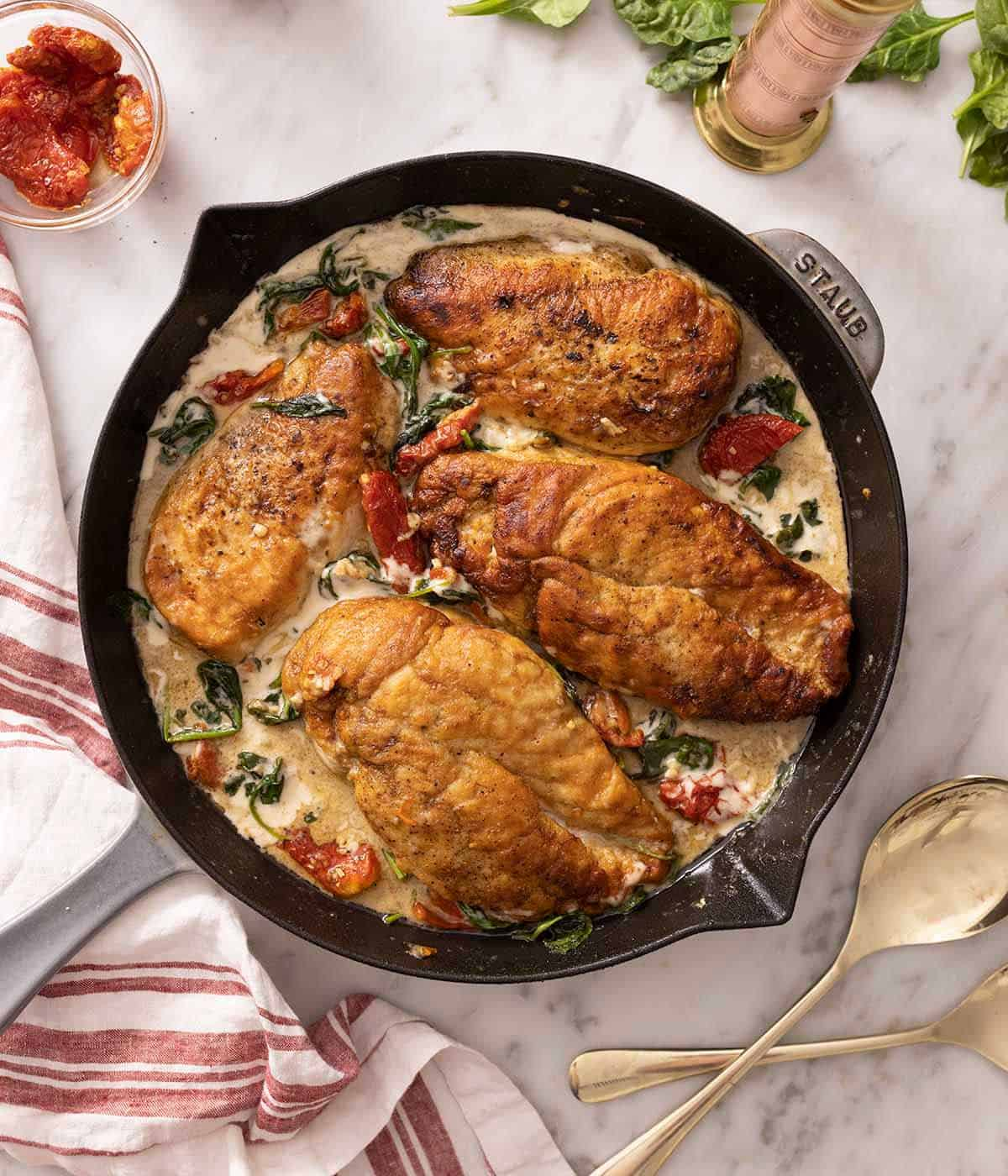 A grey Staub pan containing Tuscan chicken on a marble surface.