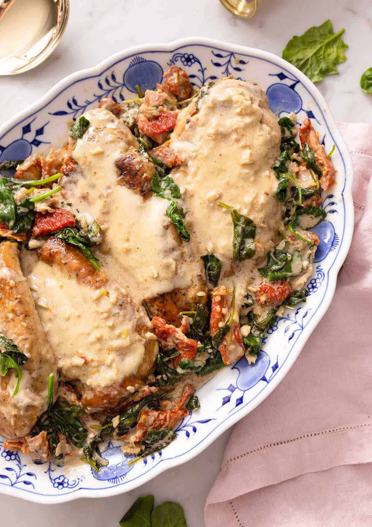 A white and blue floral platter with Tuscan chicken breasts with the sauce over top.