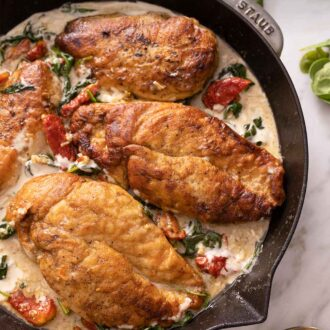 Pinterest graphic of a Staub pan with four chicken breasts in a creamy Tuscan sauce.