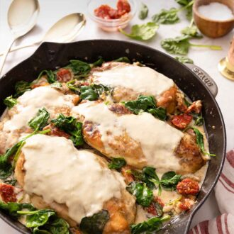Pinterest graphic of a pan of creamy Tuscan chicken with spinach and sun dried tomatoes.