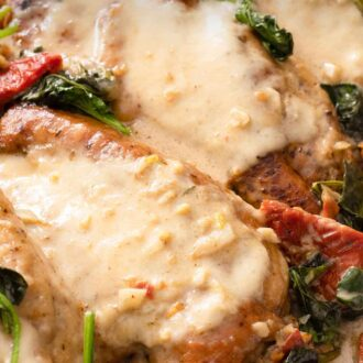Pinterest graphic of a close up of two chicken breasts that are coated with a creamy Tuscan chicken sauce.