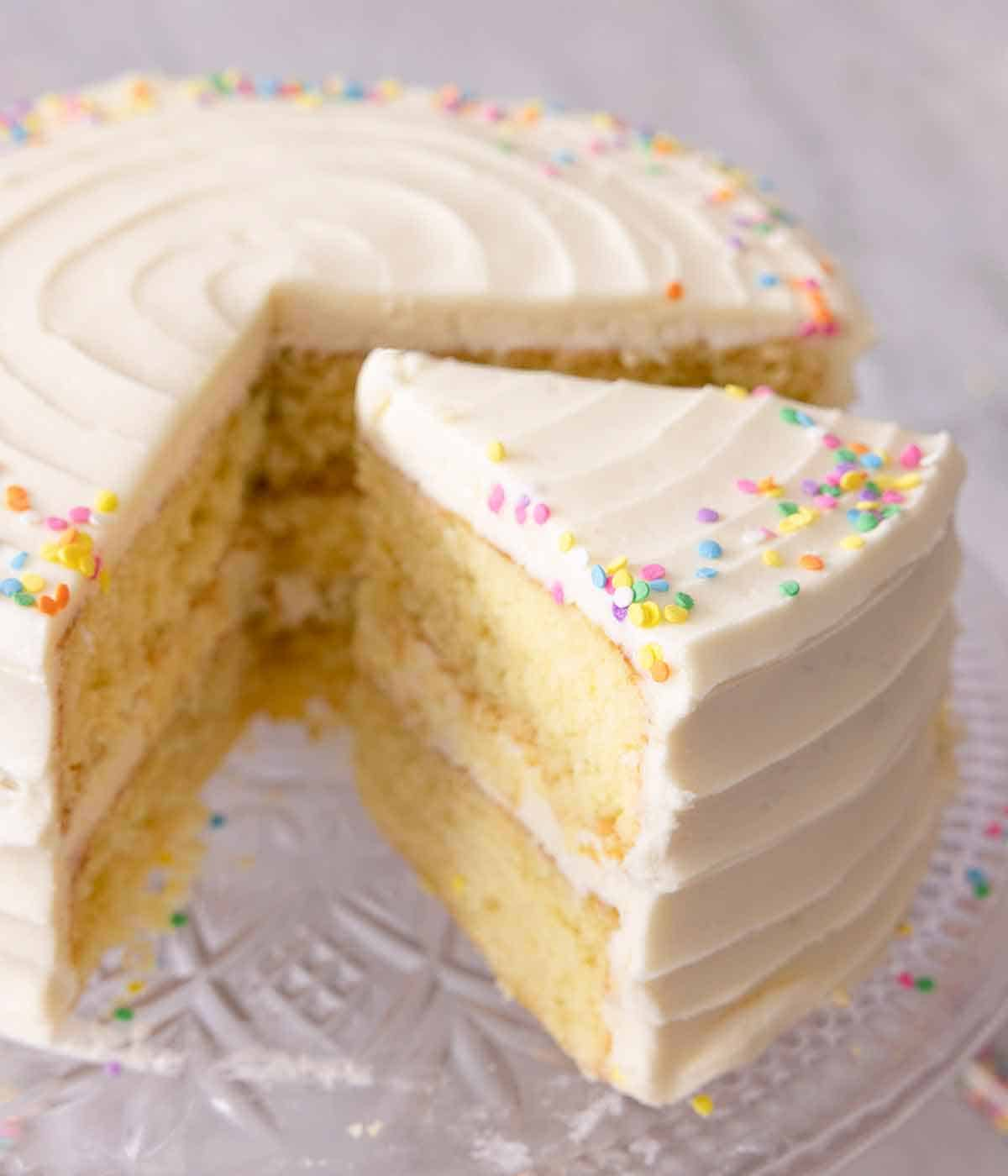 A slice of vanilla cake cut and separated from the cake.