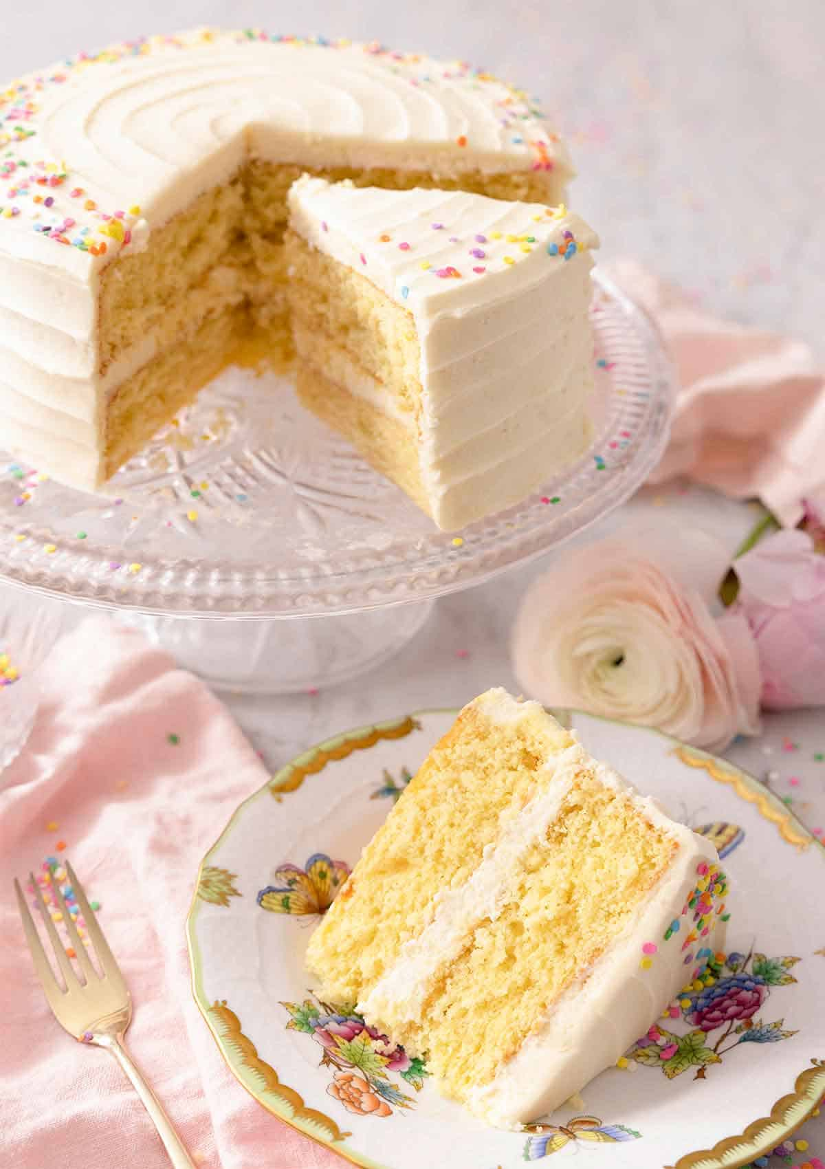 A slice of vanilla cake on a plate in front of the cake on a cake stand.