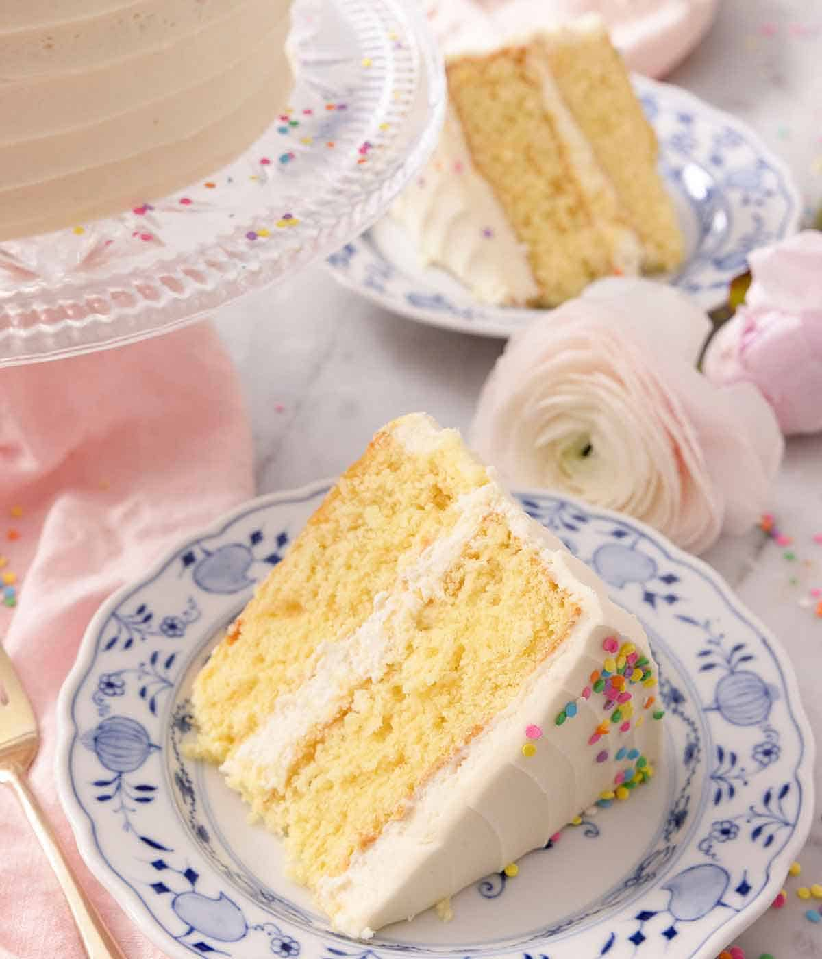 A blue plate with a slice of layered vanilla cake.