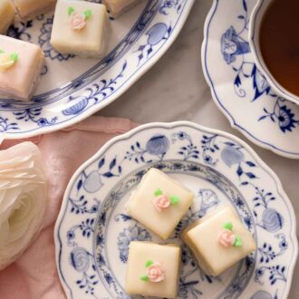 Pinterest graphic of petit fours in two plates, beside a cup of tea.