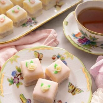 Pinterest graphic of three petit fours with small frosted flowers on top beside a cup of tea.