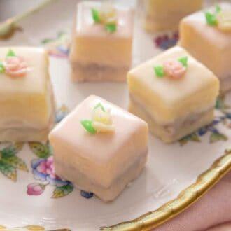 Pinterest graphic of petit fours on a serving platter beside a pink linen.