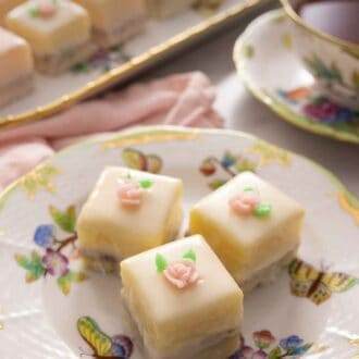 Pinterest graphic of a close up of three petit fours on a plate beside a cup of tea.