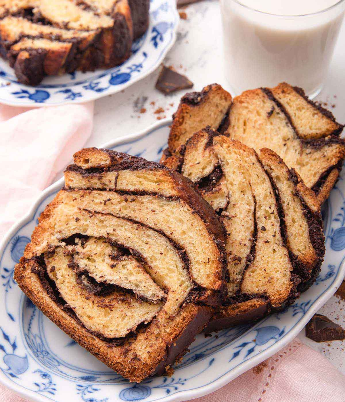 A blue and white platter with three slices of babka beside a glass of milk.