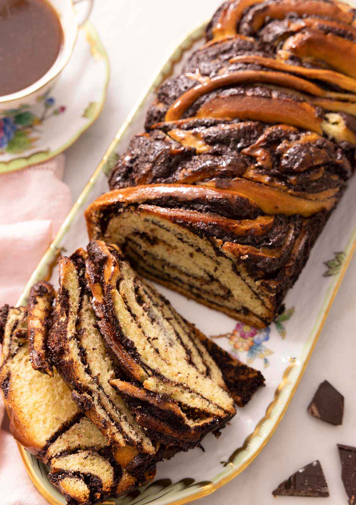 Overhead image of a babka on a long plate with three slices cut out and lying beside the loaf.