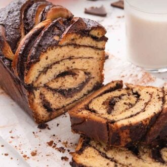 Pinterest graphic of a cut loaf of babka, with two slices in front of it, stacked on top of each other.
