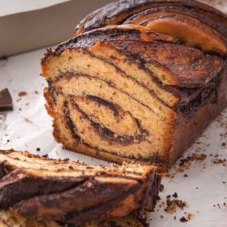 Pinterest graphic of a cut loaf of babka, showing the swirls of chocolate inside of the bread.
