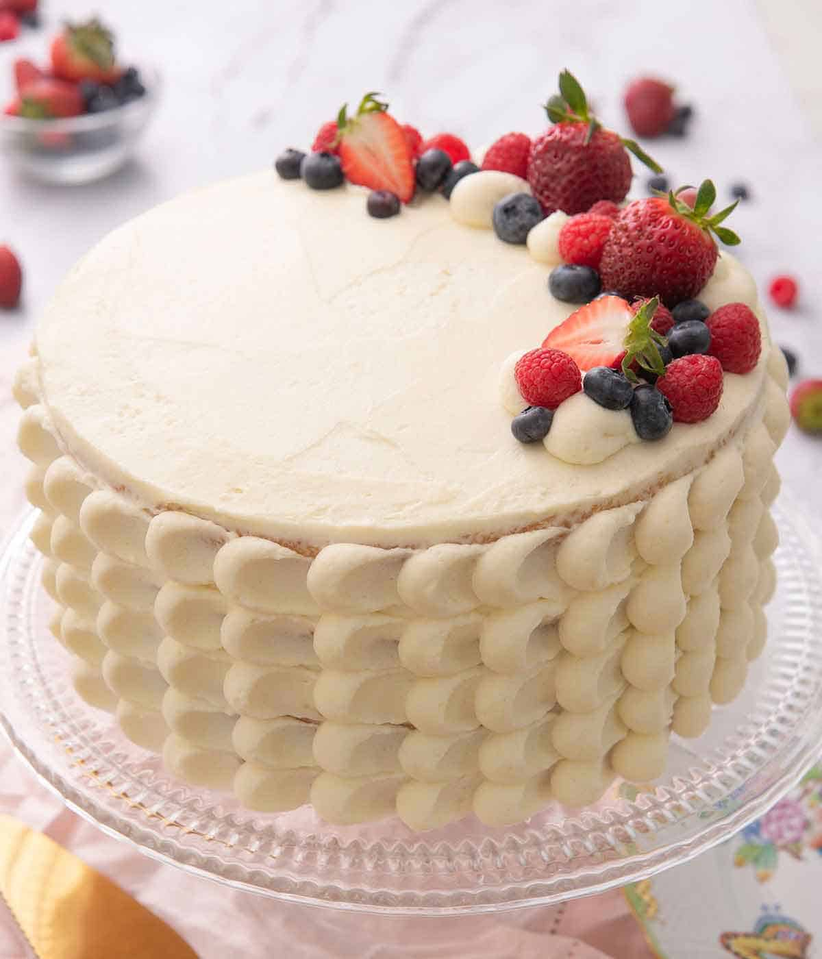 A Chantilly cake with fresh berries right aligned on the cake's top.