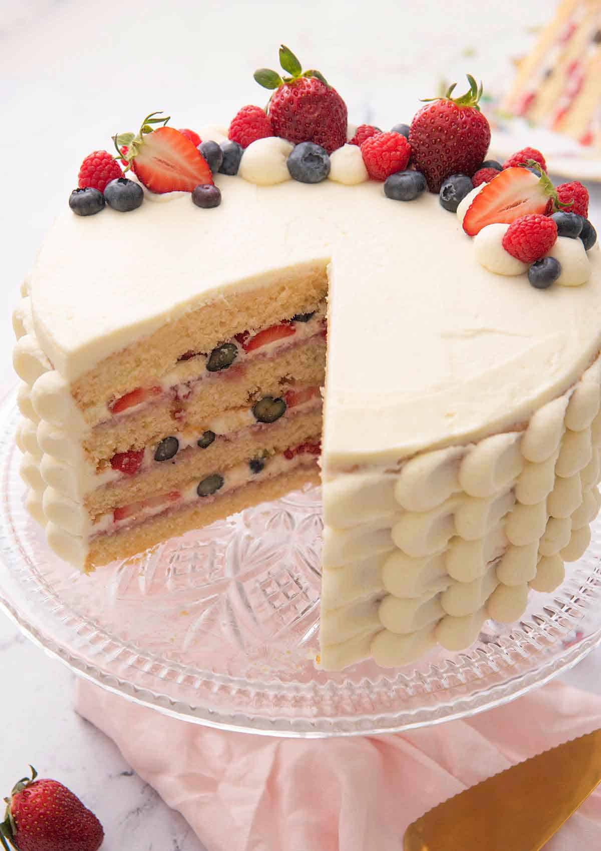 A Chantilly cake with a slice cut out showing the four tiers with berries in between.
