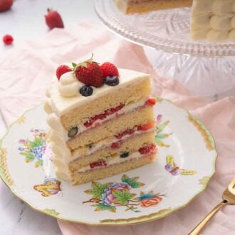 Pinterest graphic of a slice of Chantilly cake showing the layers and berries in the cream filling.