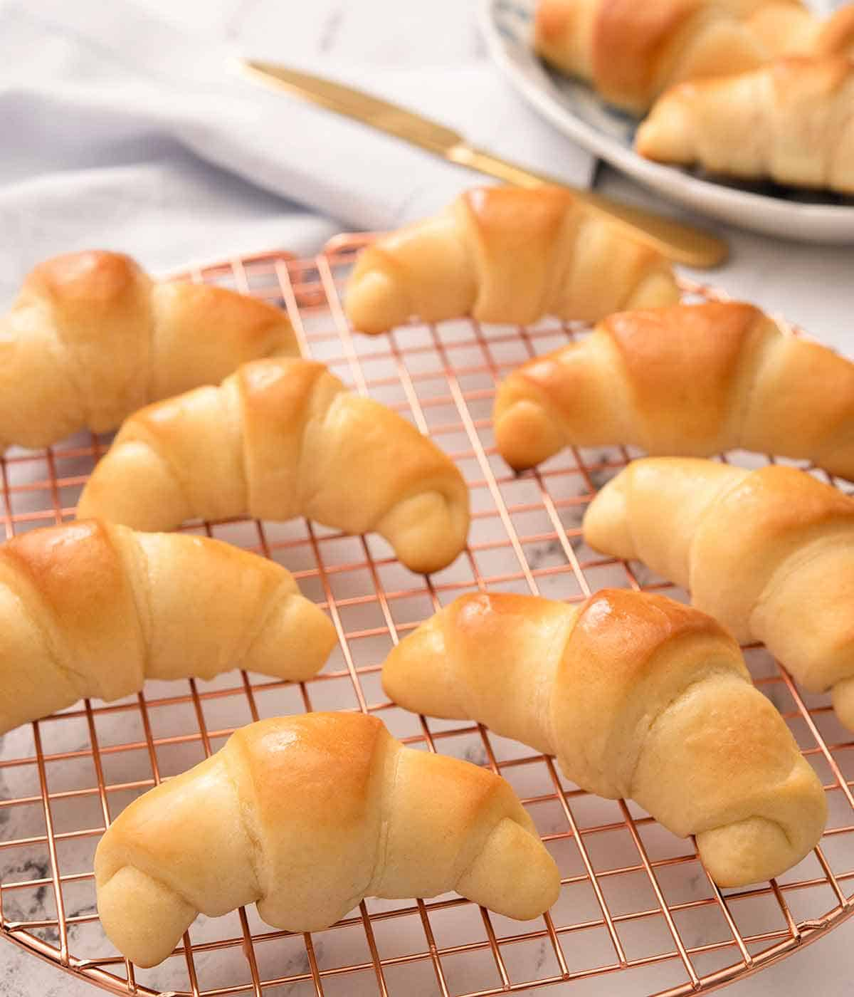 Eight crescent rolls on a rose gold circular cooling rack.