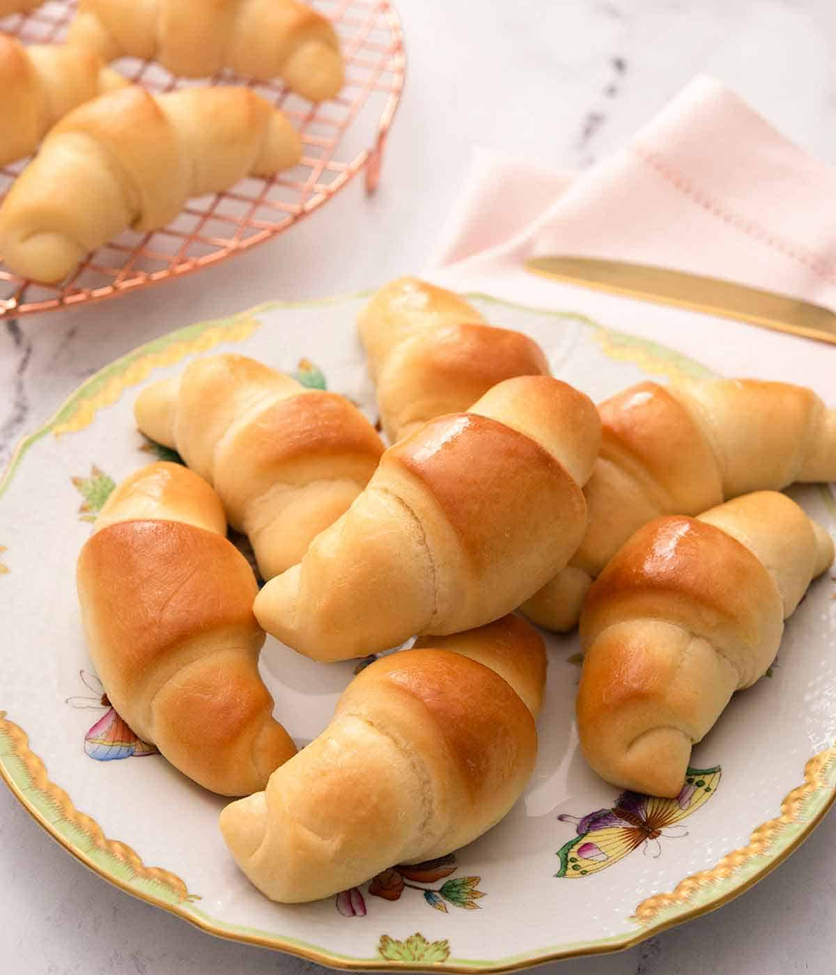 Close up of a plate of seven crescent rolls on a pink linen.