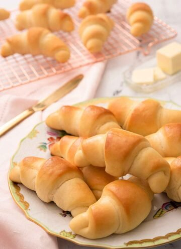 A plate of multiple crescent rolls with a cooling rack with more rolls in the background.