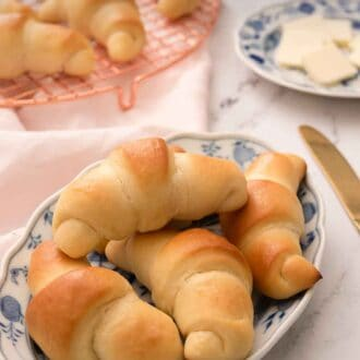 Pinterest graphic of four crescent rolls on a white and blue plate with more behind it.