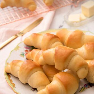 Pinterest graphic of crescent rolls piled on to a plate beside a folded pink linen napkin and a cooling rack with rolls cooling on top.