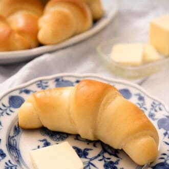 Pinterest graphic of a crescent roll on a blue and white plate with a slice of butter.