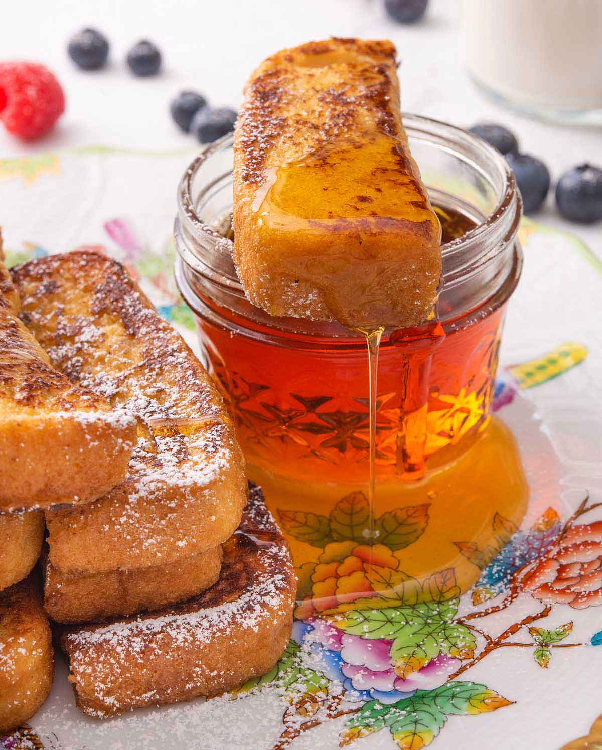 A plate with a French toast stick on top of a small mason jar of maple syrup with some dripping off the stick.