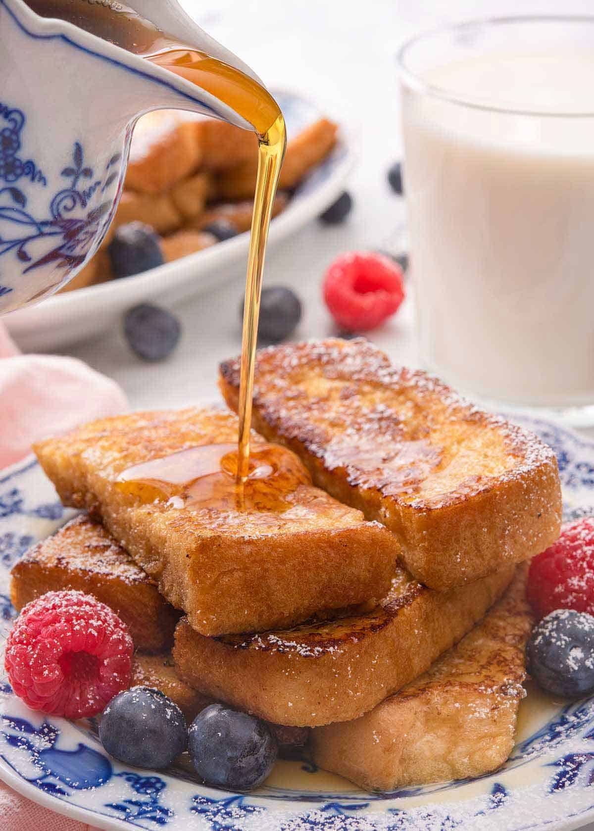 Maple syrup being poured on top of a stack of French toast sticks with fresh berries beside them.