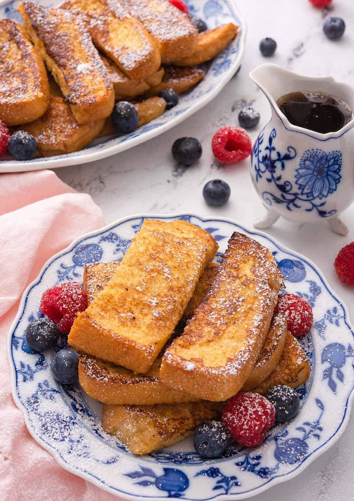 A plate of French toast sticks with powdered sugar on top and fresh berries around it. A serving platter with more is in the background along with syrup.