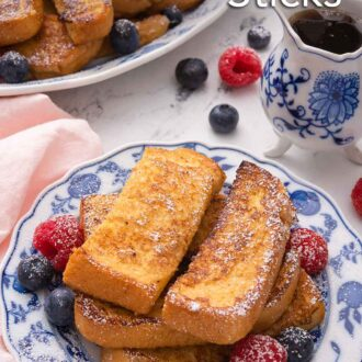 Pinterest graphic of a plate with a stack of French toast sticks and fresh fruit with a serving platter with more in the background.