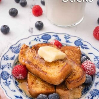 Pinterest graphic of a plate of French toast sticks with a knob of butter on top and with fresh berries beside them on the plate. A glass of milk and additional berries are in the background.