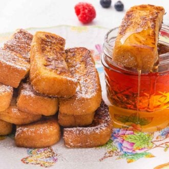 A plate with multiple French toast sticks with one on top of a mason jar of maple syrup.