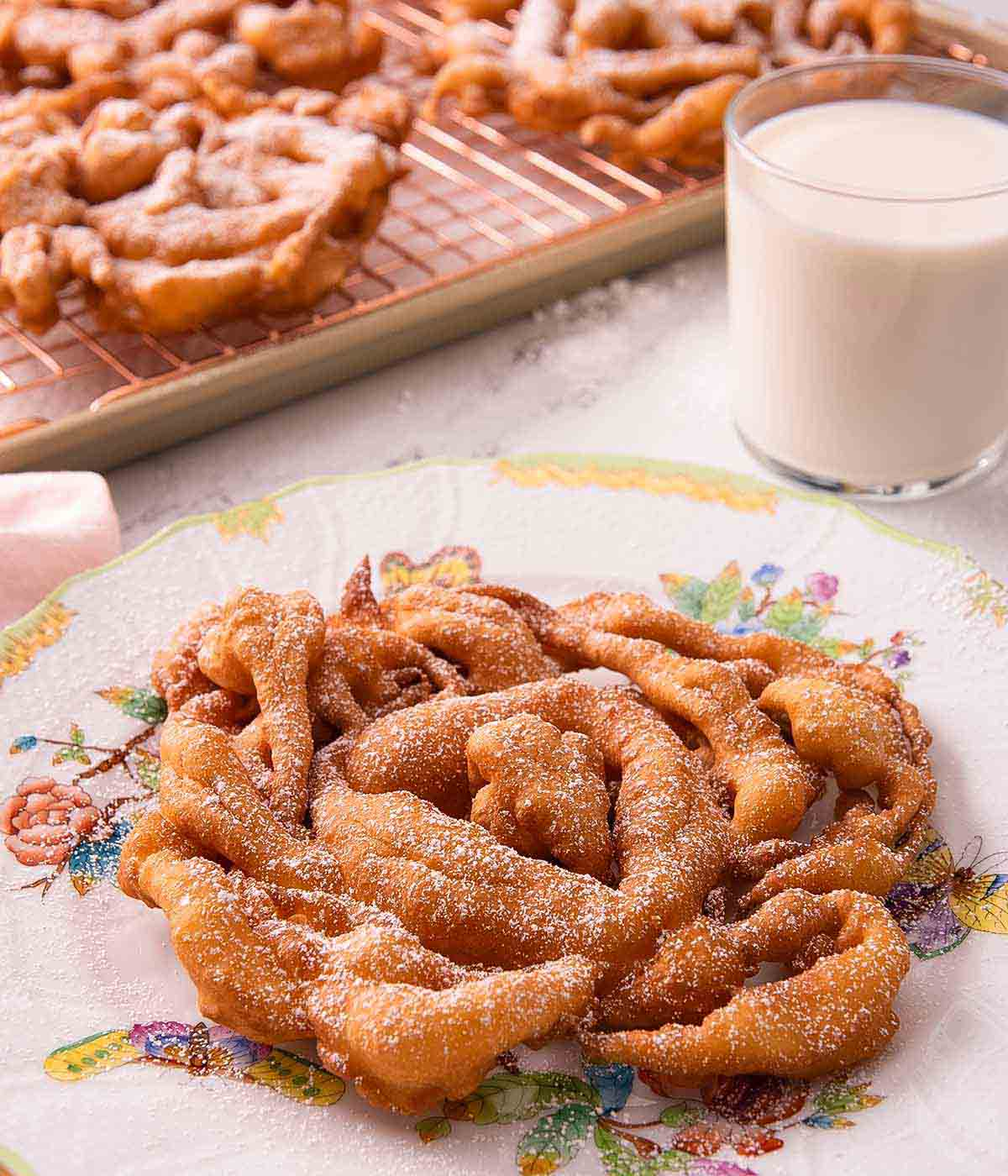 A round funnel cake with a fine dusting of powdered sugar with a glass of milk in the background and more funnel cakes on a cooling rack.