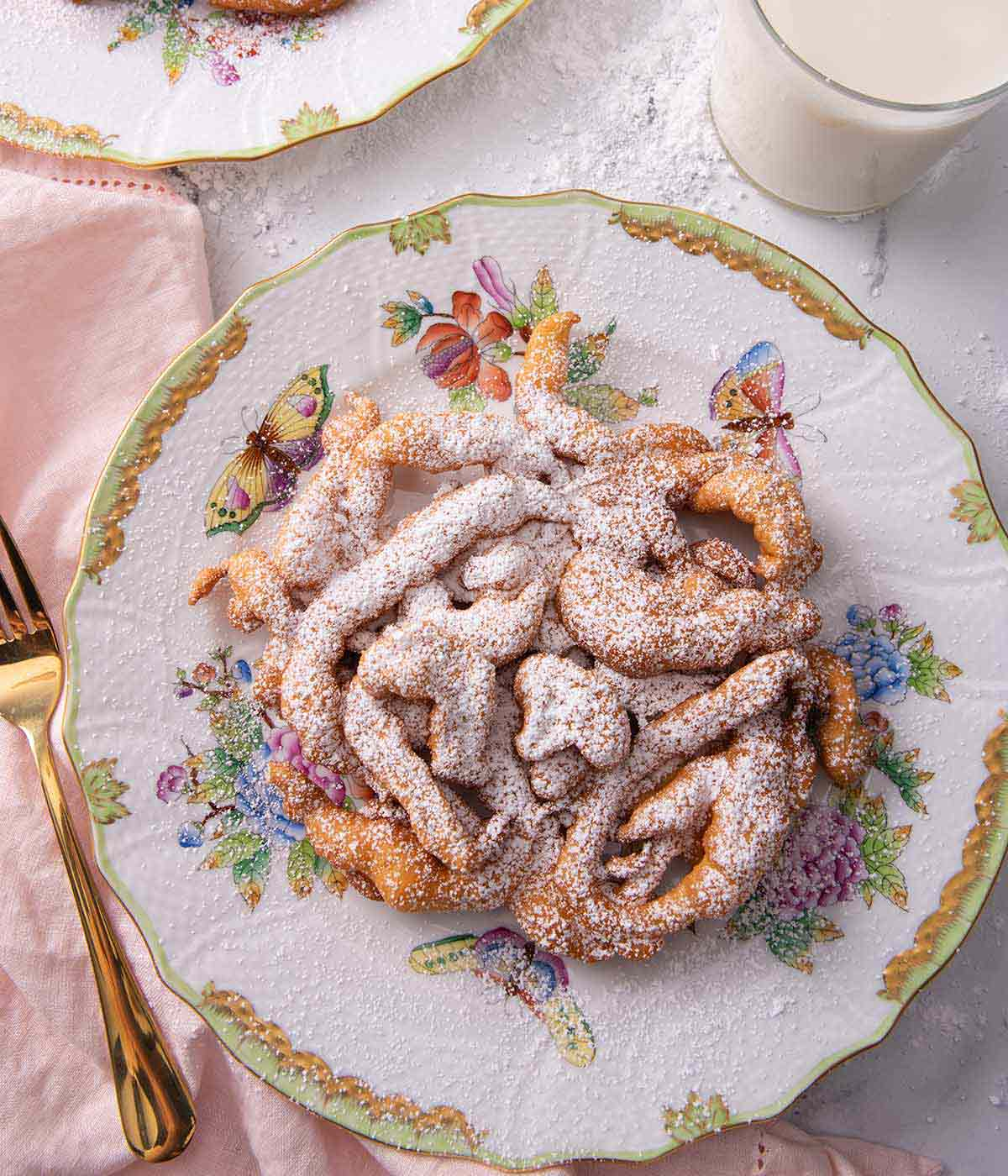 Overhead view of a powdered sugar covered funnel cake beside a gold colored fork and a pink linen napkin.