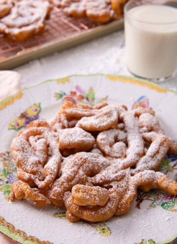 Funnel cake with a dusting of powdered sugar on a serving plate with a glass on milk in the background.