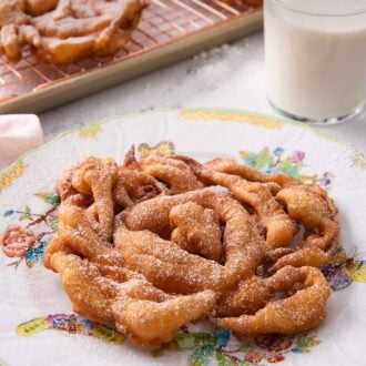 Pinterest graphic of a funnel cake on a plate with more in the background on a cooling rack.