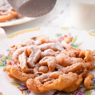 Pinterest graphic of powdered sugar being dusted onto a funnel cake.