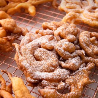 Pinterest graphic of a cooling rack with multiple funnel cakes with two with powdered sugar.
