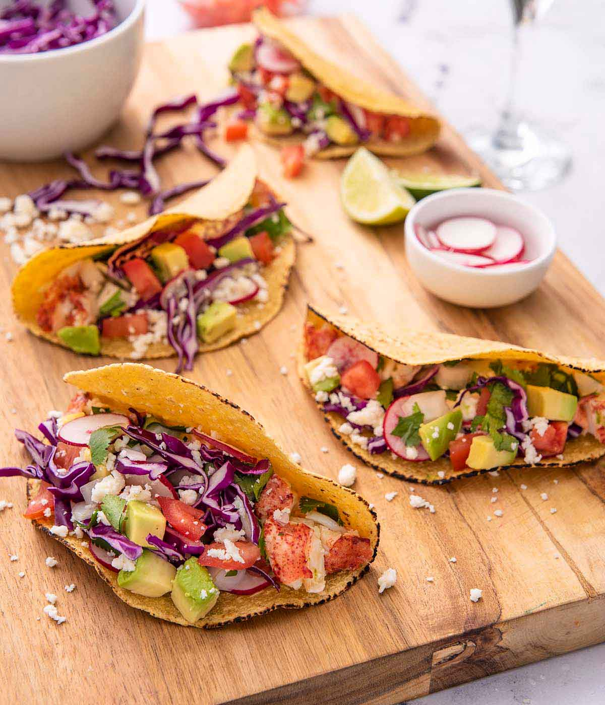 A brown cutting board with four lobster tacos with a pinch bowl of sliced radishes and a bowl of cabbage on the board.